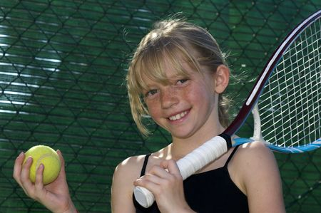 Confident Elementary Age Girl with Tennis Ball and Racket. Banque d'images
