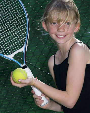 Confident Elementary Age Girl with Tennis Ball and Racket. 免版税图像