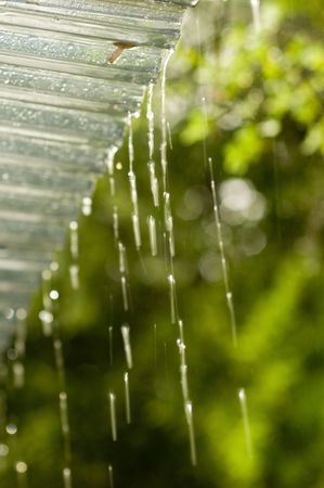 drenched: Rain dripping from patio roof edge. Shallow DOF.