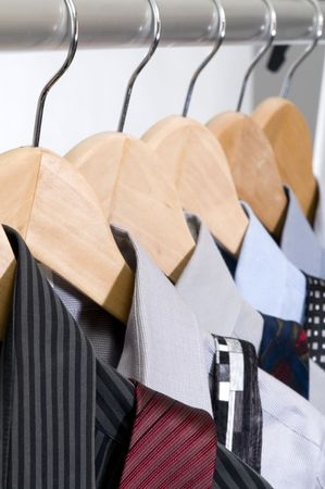 Dress shirts and ties on wooden hangers.