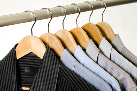 Dress shirts on wooden hangers.