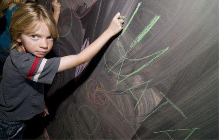 elective: Elementary School Kid Drawing on a Blackboard
