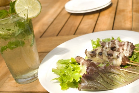 Delicious Beef or Pork Satay and a refreshing Mojito in a tropical setting. photo