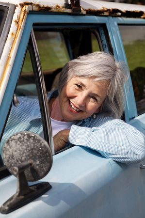 Smiling senior taking a cruise in the old rustbucket Imagens