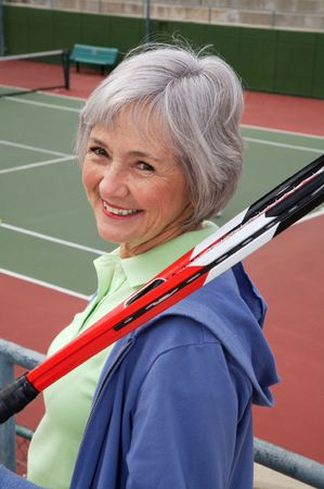 Active senior on the tennis court. 免版税图像