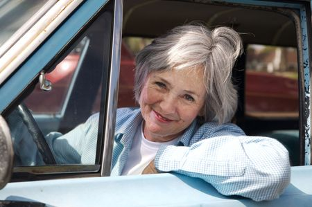 aging: Smiling senior taking a cruise in the old rustbucket Stock Photo