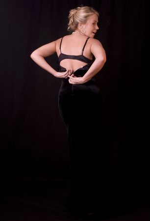 Beautiful Blonde Unzipping Black Evening Gown 版權商用圖片