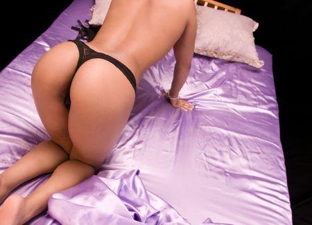 Beautiful girl in panties kneeling on silk sheets.