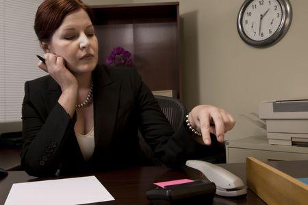 office stapler: Bored office worker tapping the stapler