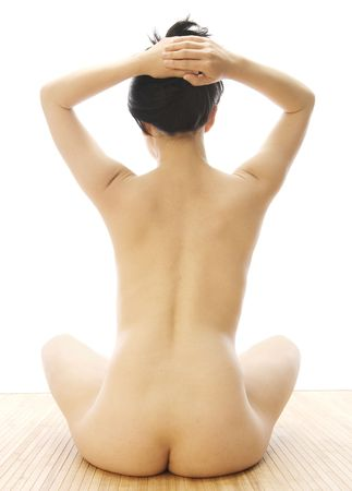 Rearview of delicate nude in yoga position on bambo mat. photo
