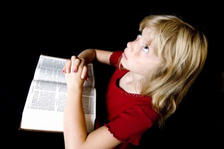 Angelic little girl saying her prayers over an open New Testament.