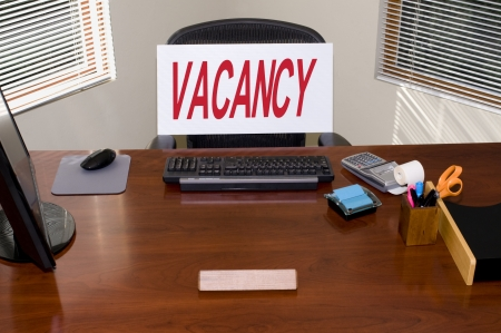 job loss: Desk with a Vacancy sign.  Your text in the blank name plate.  Great for employmentHRunemployment themes. Stock Photo