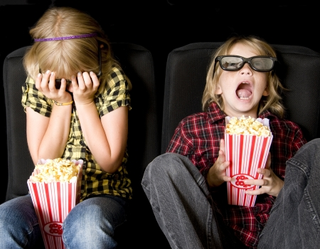 horror movies: Frightened Boy and Girl Wearing New Style 3-D Glasses in a Movie Theater