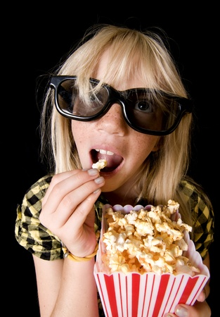 Happy Girl Wearing New Style 3-D Glasses in a Movie Theater photo