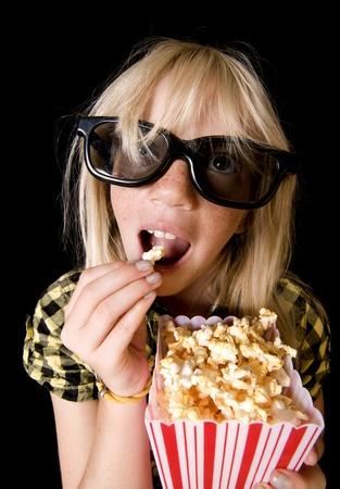 scared child: Ni�a feliz llevando gafas 3D nuevo estilo en una sala de cine Foto de archivo