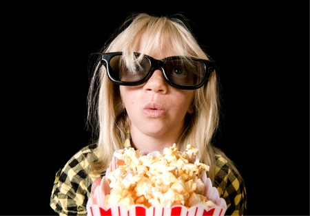 Girl Wearing New Style 3-D Glasses in a Movie Theater photo