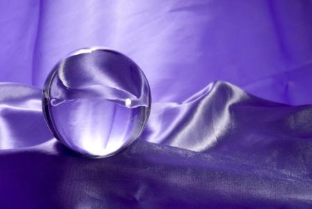 stock predictions: Una sfera di cristallo sul tessuto viola.