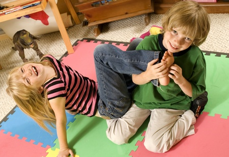 Adorable twins wrestling/playing keep-away on the playroom floor.