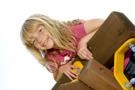 jungle gym: Young Girl Climbing on a Jungle Gym Stock Photo