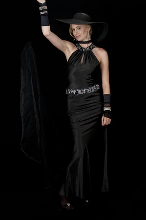 High fashion model in black satin cocktail gown dropping her veil.