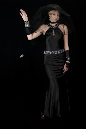 High fashion model in black satin cocktail gown dropping her bracelet. 免版税图像
