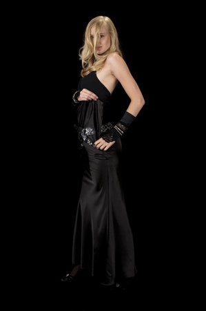 High fashion model in black satin cocktail gown removing her dress.
