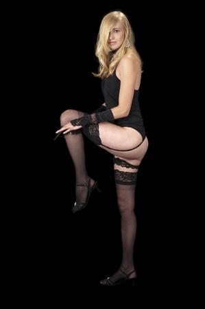 High fashion model in black lingerie removing her garter. Stock Photo