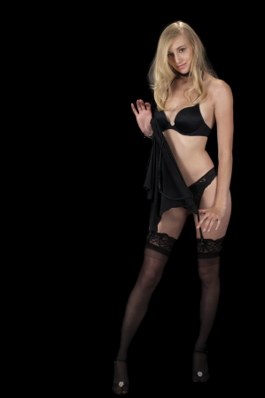 The Evening Wear Striptease Sequence: High fashion model in black lingerie removing her camisole. Stock Photo