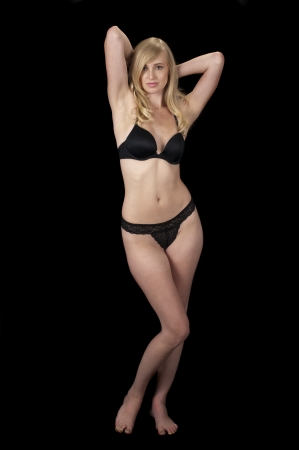 The Evening Wear Striptease Sequence: High fashion model in black lingerie unfastening her bra. photo