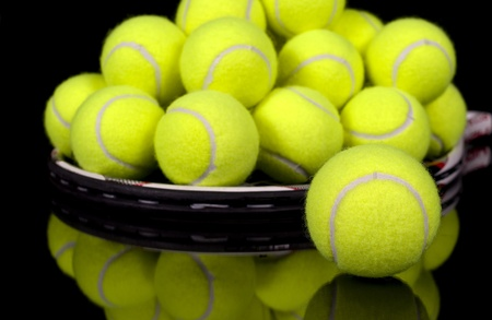 Pile of tennis balls on tennis racket isolated on black reflective surface  Stock Photo