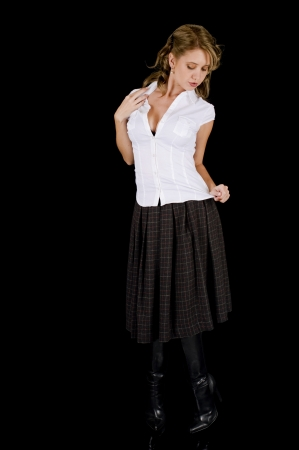 A cute young woman posing seductively in her white shirt and plaid skirt. photo