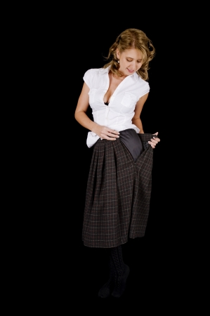 A cute and fresh-faced young woman is removing her plaid skirt