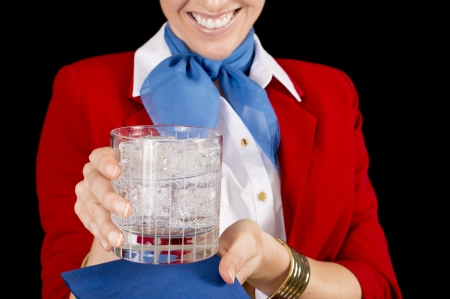 An unidentifiable flight attendant o rrestaurant server offering a refreshing beverage.  Focus on the drink.