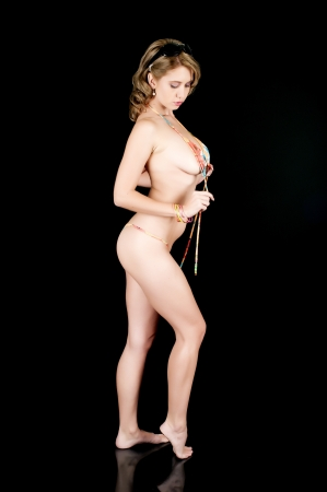 woman nude standing: Young girl posing in a string bikini and untying her top Stock Photo