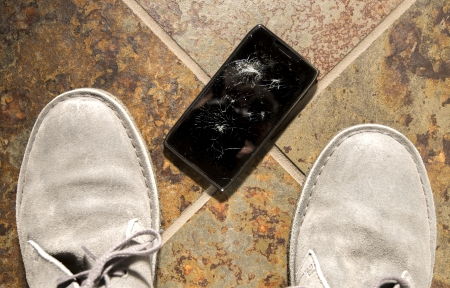 broken telephone: A smartphone lies broken between the shoes of its owner just after being dropped. Stock Photo