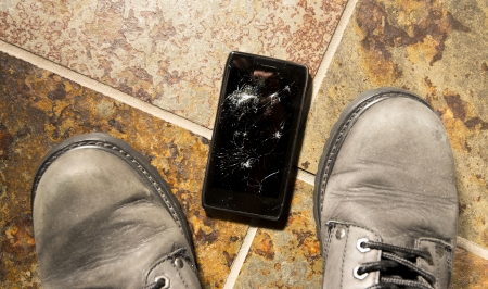 portable failure: A smartphone lies broken between the workboots of its owner just after being dropped.