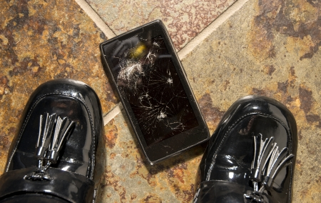 portable failure: A smartphone lies broken between the shoes of its businesswoman owner just after being dropped. Stock Photo