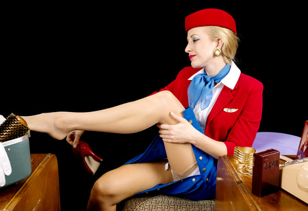 airline hostess: Retro airline hostess removing her stockings and shoes
