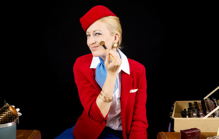 an attendant: Retro Airline Stewardess or Flight Attendant Applying Make-up with a Brush at her Vanity