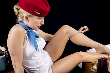 Retro airline hostess removing her stockings