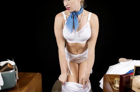 girl undressing: Retro airline hostess removing her satin slip.
