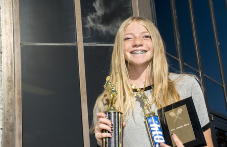 A Happy Teenage Girls Tennis Player Showing Off Her Trophies photo