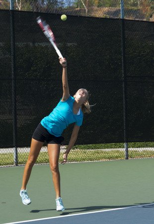 Junior competitive girls tennis player displaying excellent service technique.  Motion blur. Stock Photo
