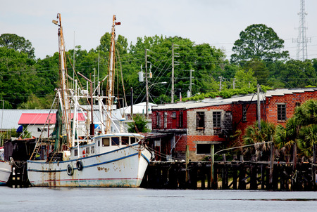Shrimp boat docked at a wooden pier in North Carolina