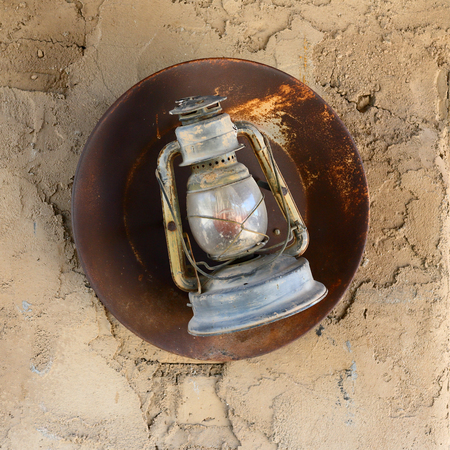 Antique lantern with rusted reflector hanging on an adobe wall