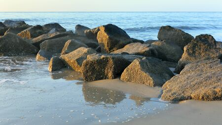 Early morning at the south end of Tybee Island beach with a rock jetty Banco de Imagens