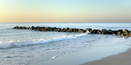 Early morning at the south end of Tybee Island beach with a rock jetty Stok Fotoğraf