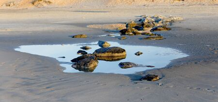 Early morning at the south end of Tybee Island beach with a rocks in a pond