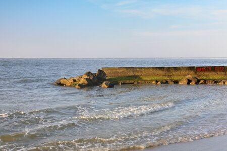Early morning at the south end of Tybee Island beach with a jetty and islands across the water