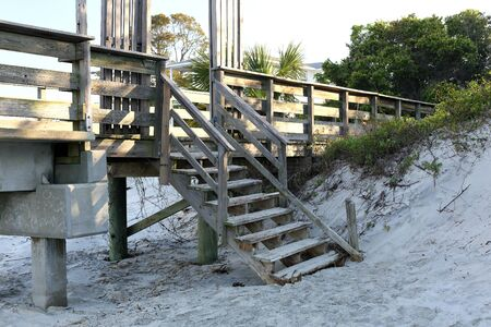 A wooden stairway from the beach to a fishing pier is in need of repair